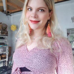 White woman looking at camera wearing pink top