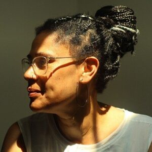 Black woman with head turned to the left waring glasses, braid hair in a bun